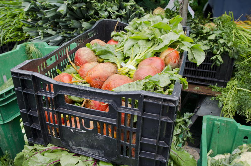 Beets. A crate of orange beets among other vegetables for sale at the outdoor farm market stock images
