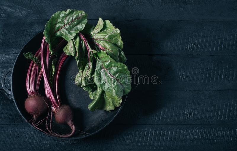 Beets with green tops in round metal pan on dark black wooden background, fresh red beetroot on backdrop kitchen table top view,. Healthy vitamin vegan food stock photos