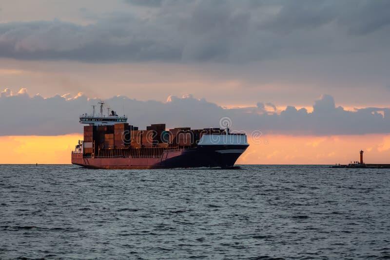 Befördern Sie Schiff auf dem hellen Gehen des Sonnenuntergangs vom Hafen zur Ostsee stockbild