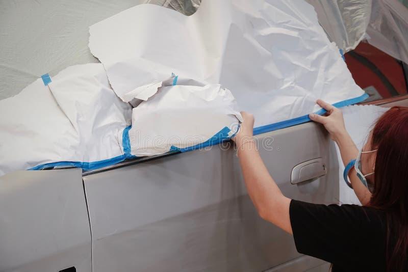 Befestigen Sie das Papier zur Sprühfarbegaragen-Fahrzeugkarosseriearbeits-Autoreparaturfarbe nach dem Unfall während des Sprühens lizenzfreies stockbild