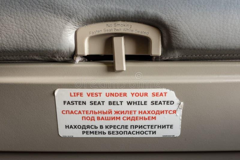 Befestigen Sie Sicherheitsgurt während Sitzsymbol auf der Rückseite eines Flugzeugsitzes lizenzfreie stockbilder