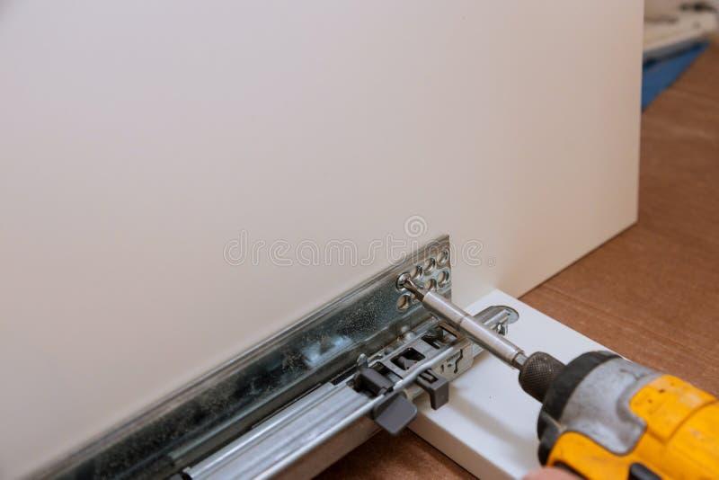 Befestigung Scharniere für die Möbelzusätze benutzt, wenn Küchenmöbel zusammengebaut werden stockbild
