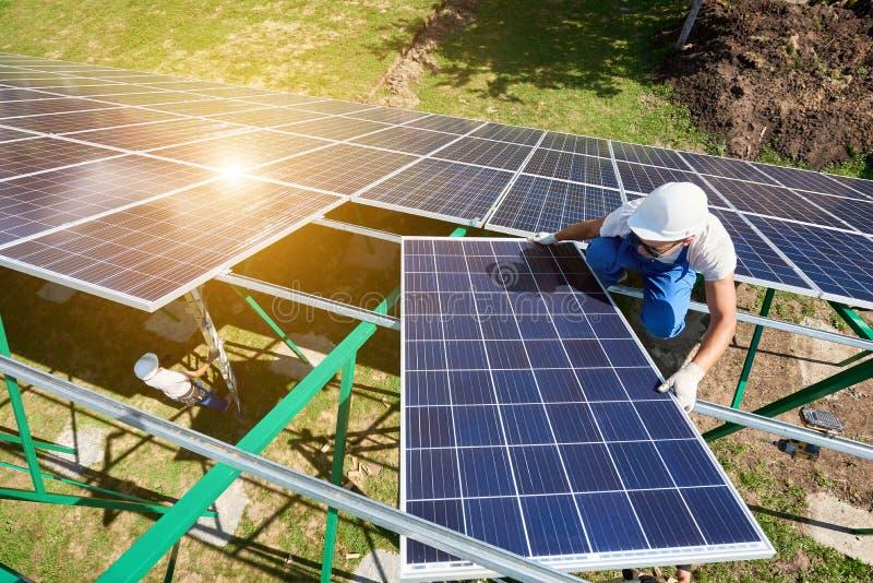 Befestigung von Solarbatterien an der grünen metallischen Karkasse durch Berufsarbeitskräfte lizenzfreie stockfotos