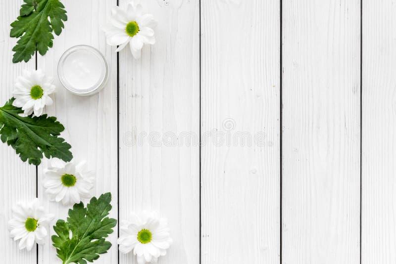 Befeuchten auf Cremebasis von den natürlichen Kräuterbestandteilen Kamillencreme im kleinen Glas nahe Kamille blüht auf Weiß stockfotos