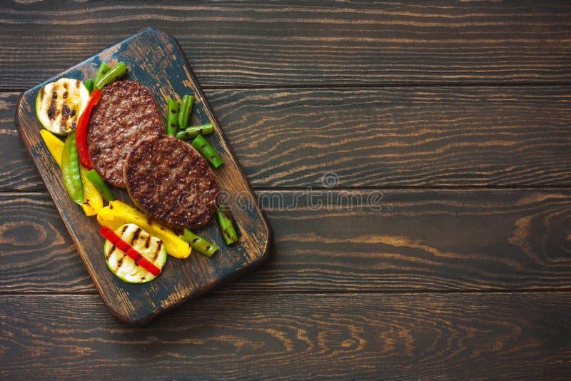 Befsztyk piec na grillu z warzywami na ciemnym drewnianym tle fotografia royalty free