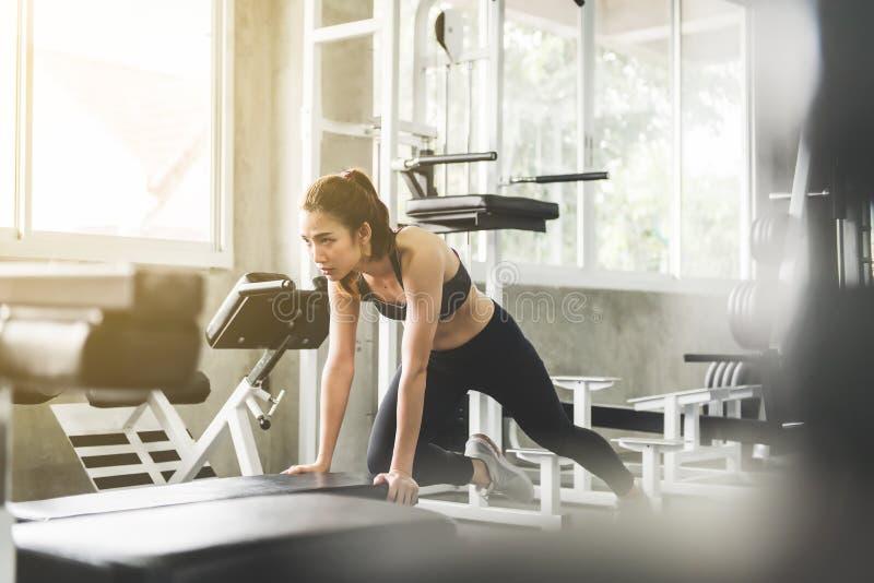 Begås som asiatiska kvinnaögon för sporten gör övningsutbildning på bänk, den arg färdiga kroppen och muskulöst i idrottshall royaltyfri fotografi
