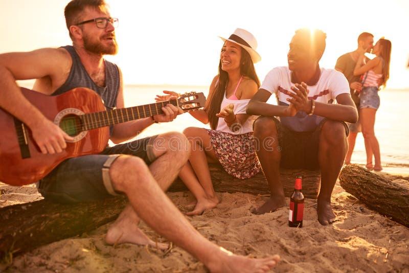 Begåvad gitarrist som spelar gitarren för vänner på stranden royaltyfri fotografi