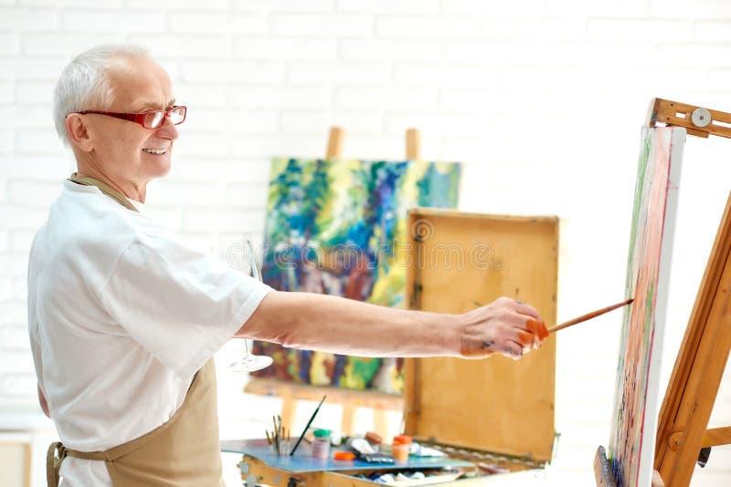 Begåvad manlig målareteckningsbild i konststudio genom att använda målarfärg och borsten arkivfoton