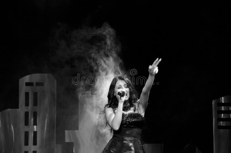 Begåvat och idérikt Stående av den nätta unga sexiga stilfulla kvinnan som sjunger på etapp på mikrofonen royaltyfri fotografi
