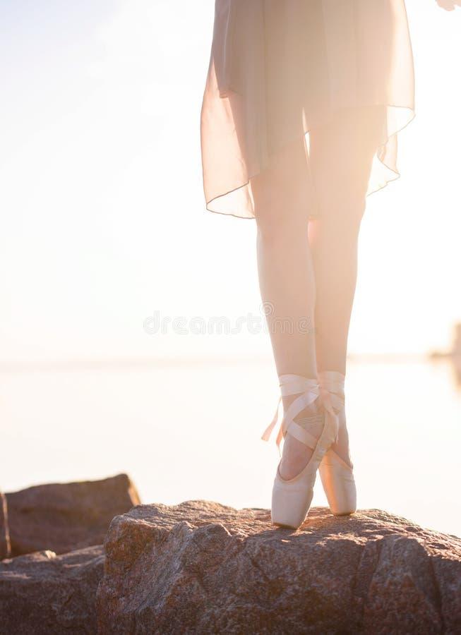 Begaafde ballerina met pointeschoenen op het strand bij zonsondergang stock foto