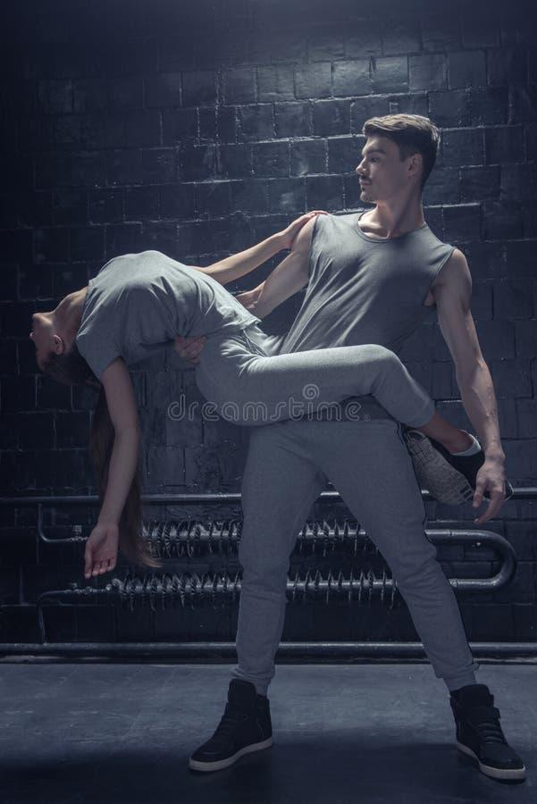 Begaafde dansers die in dichte interactie met elkaar presteren stock afbeeldingen