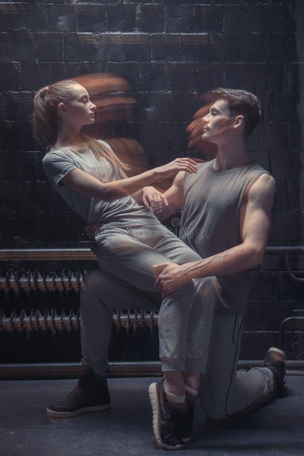 Begaafde danserszitting op het been van andere atleet royalty-vrije stock foto's