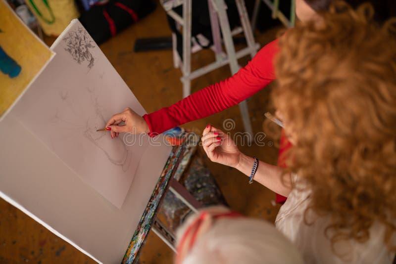 Begabte Künstler, die Vase auf Segeltuch sprechen und zeichnen stockbilder