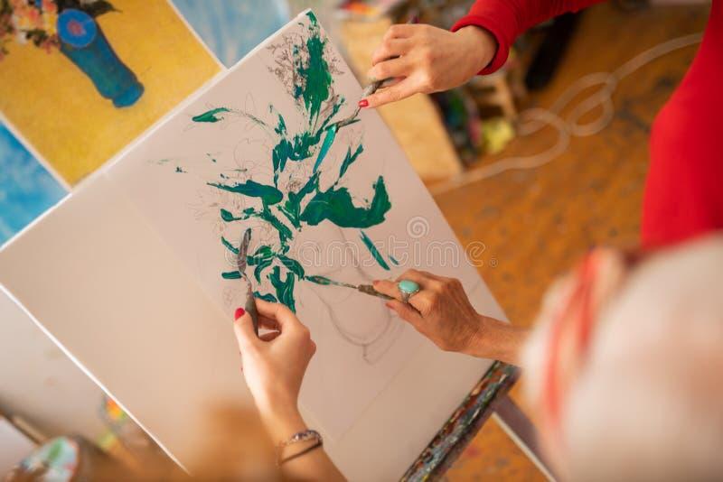 Begabte Künstler, die Vase mit Anlagen und Blumen färben stockfotos