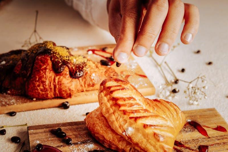 Begabter Bäcker, der Windbeutel mit Nüssen in der Schokolade verziert stockbild