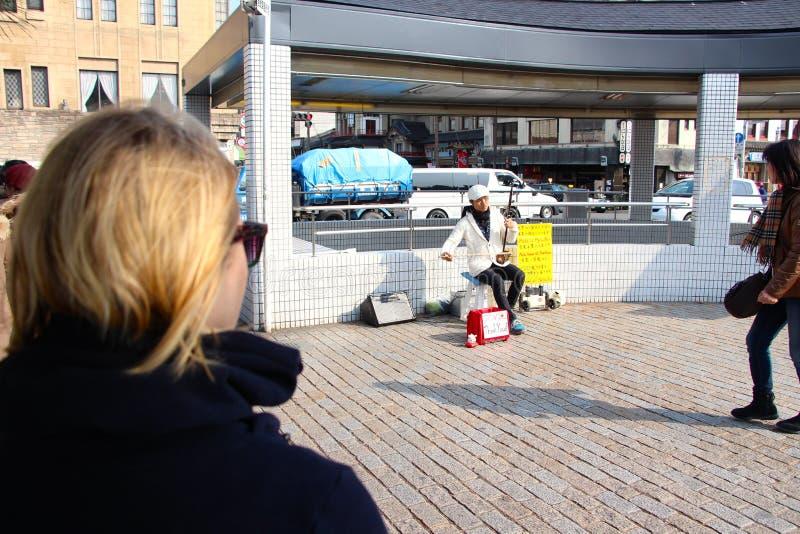 Begabter japanischer Straßenausführender, der an den Ampeln busking ist stockfotografie
