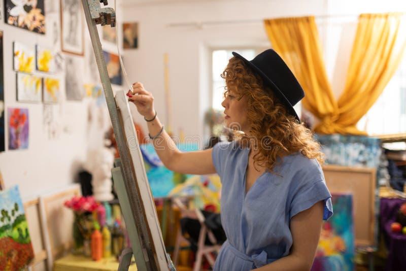Begabter junger Künstler, der blaue Kleidermalerei auf Segeltuch trägt lizenzfreie stockbilder