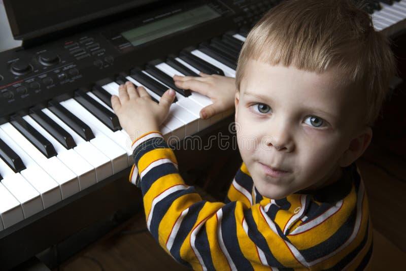 Begabter kleiner Junge, der am Klavier sitzt stockfotografie