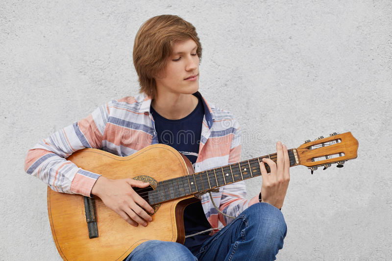 Begabter Teenager mit dem tragenden Hemd und Jeans der modischen Frisur, welche die Akustikgitarre spielt seine Lieblingslieder b stockfotografie