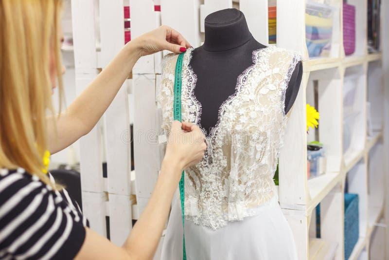 Begabter weiblicher Modekünstler, der Brautkleid herstellt stockfotos