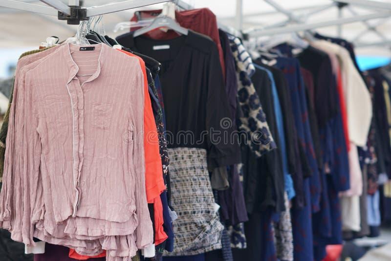 Begagnad kläder som hänger på ett stånd arkivbilder