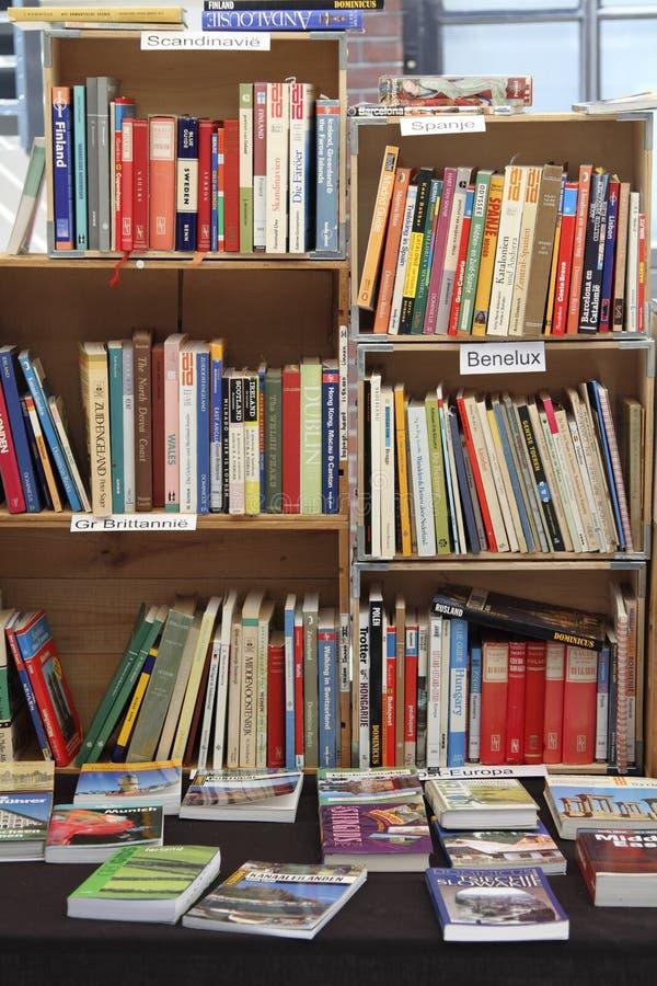 Begagnade böcker som visas i ett bokfall arkivfoton