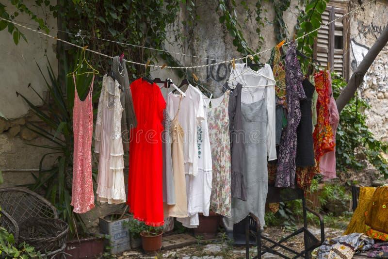 Begagnade klänningar som hänger på ett rep som säljs i det Plaka området av Aten, Grekland royaltyfri bild