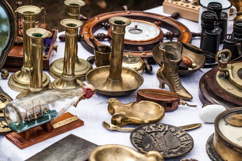 Begagnade mässingsstearinljushållare på den antika återförsäljaren visar royaltyfri fotografi