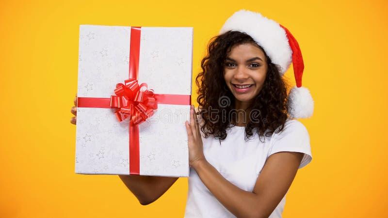Begeisterte afroe-amerikanisch Frau in Sankt-Hut, der großen Präsentkarton, Glück hält lizenzfreie stockfotografie