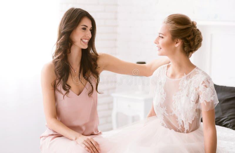 Begeisterte Brautjungfer beglückwünscht die Braut mit ihrem Hochzeitstag stockbild
