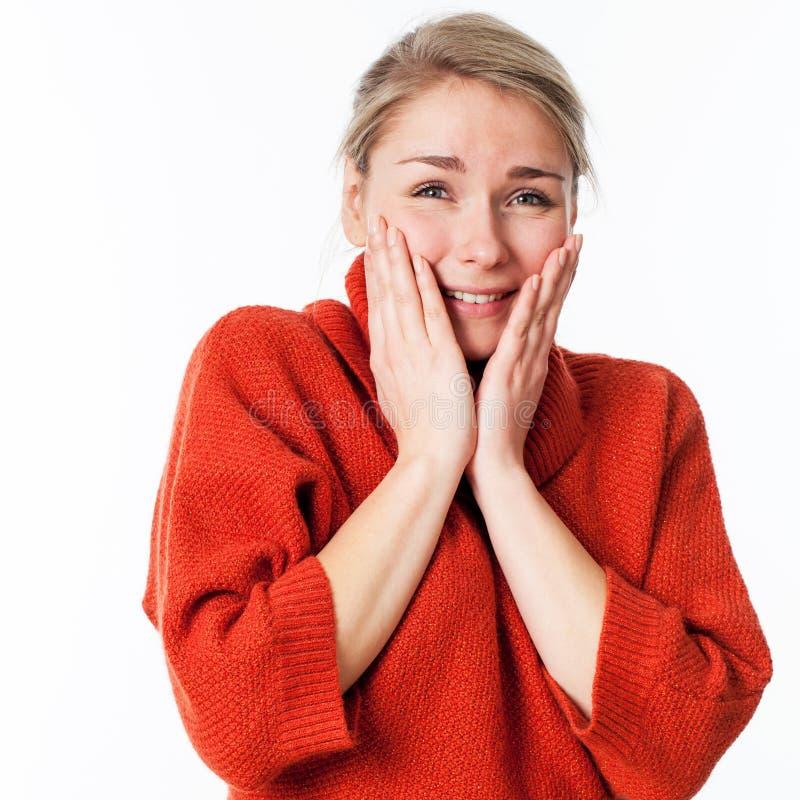 Begeisterte Frau, die ihr Gesicht für Wohl und Vergnügen berührt stockbild