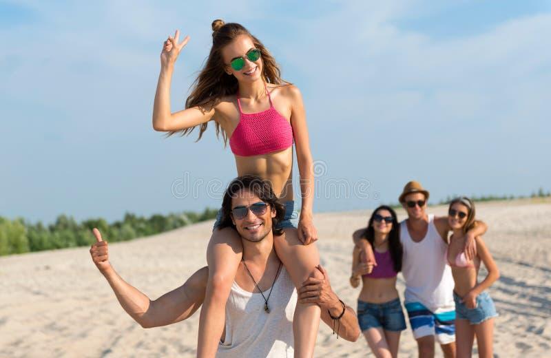 Begeisterte frohe Freunde, die Spaß auf dem Strand haben lizenzfreie stockbilder
