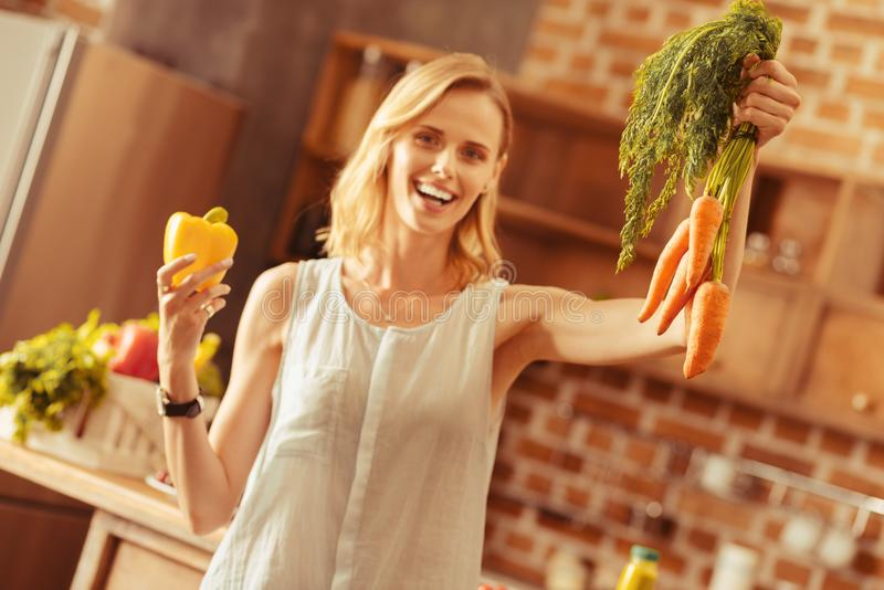 Begeisterte junge Frau, die Produkte zeigt stockfoto