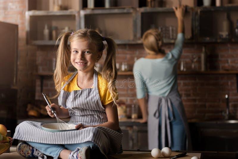 Begeisterte mischende Eier des kleinen Mädchens, die auf dem Tisch sitzen lizenzfreie stockfotos