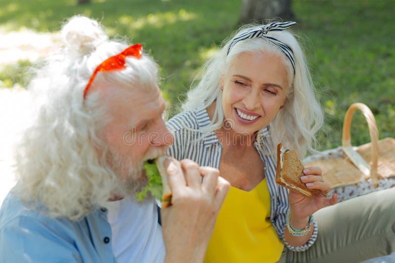 Begeisterte nette Frau, die ein Sandwich hält stockfotos