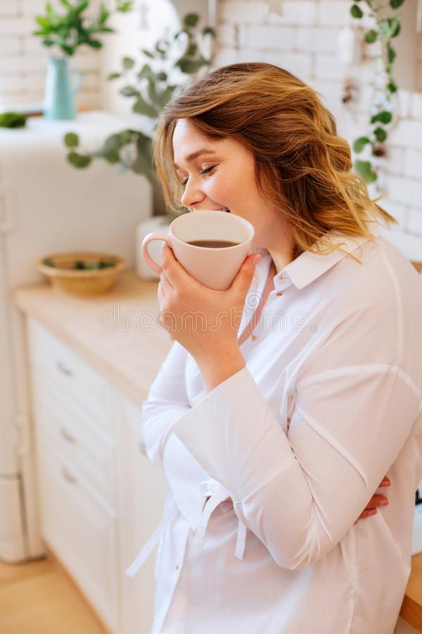 Begeisterte positive Frauenstellung mit einem Tasse Kaffee lizenzfreie stockfotografie
