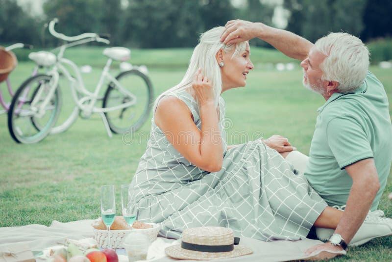 Begeisterte schöne Frau, die ihre Ohrringe zeigt lizenzfreie stockfotos