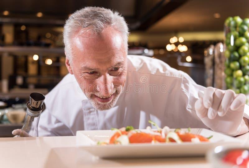 Begeisterter Chef, der die letzten Korrekturen von seinem Teller macht lizenzfreie stockfotografie