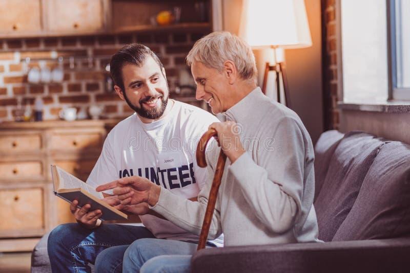 Begeisterter Freiwilliger, der ein Buch für einen Pensionär liest stockfotos