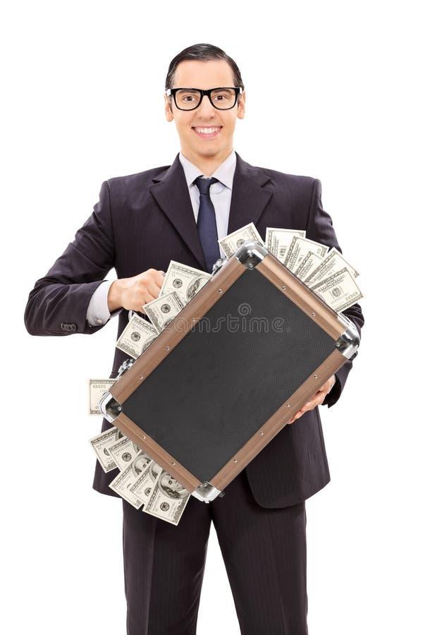 Begeisterter Geschäftsmann, der einen Aktenkoffer voll vom Geld hält lizenzfreie stockbilder
