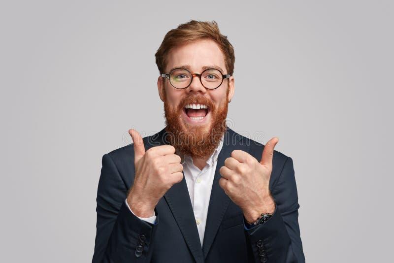 Begeisterter kühler Geschäftsmann, der sich Daumen zeigt stockbilder