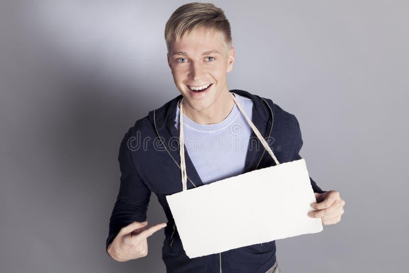 Begeisterter Mann, der Finger auf weißes leeres Schild zeigt. stockfotografie