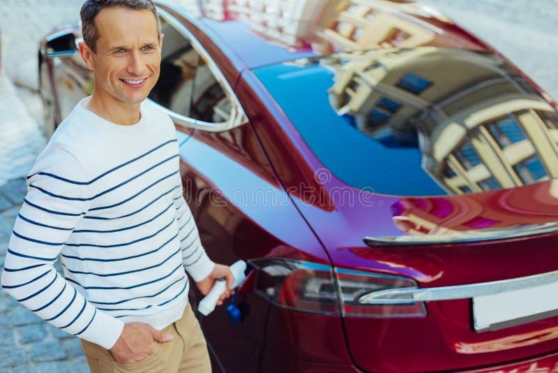 Begeisterter netter Mann, der eine Zapfpistole in das Auto setzt stockbild