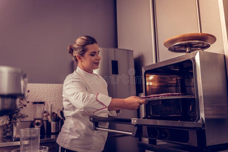 Begeisterter positiver Chef, der Behälter mit Muffins in den Ofen setzt stockbilder