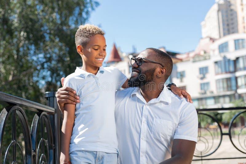 Begeisterter positiver Mann, der seinen geliebten Sohn umarmt lizenzfreies stockfoto