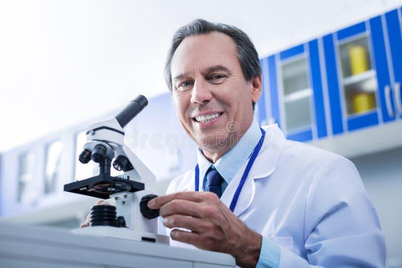 Begeistertes intelligentes erforscht das Sitzen vor dem Mikroskop stockfotografie