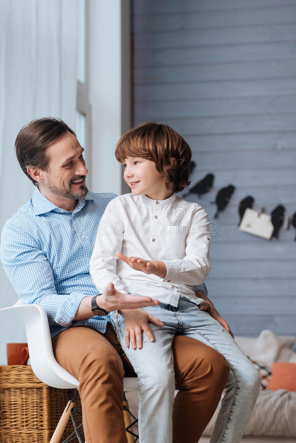 Begeistertes Kleinkind, das auf seinen Vaterknien sitzt stockfotos