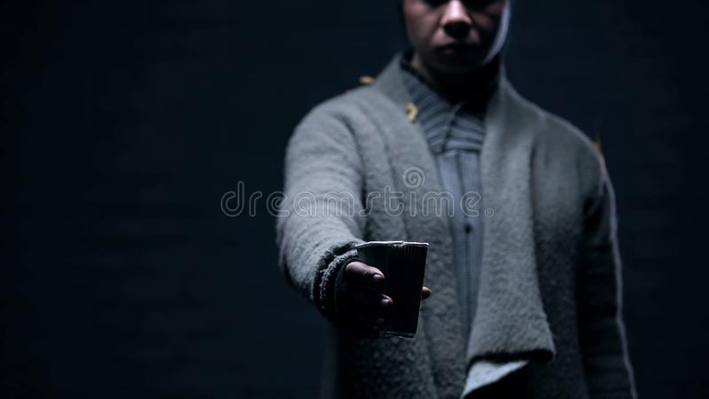 Beggar asking for donations holding paper cup in hand, unemployment poverty stock photography