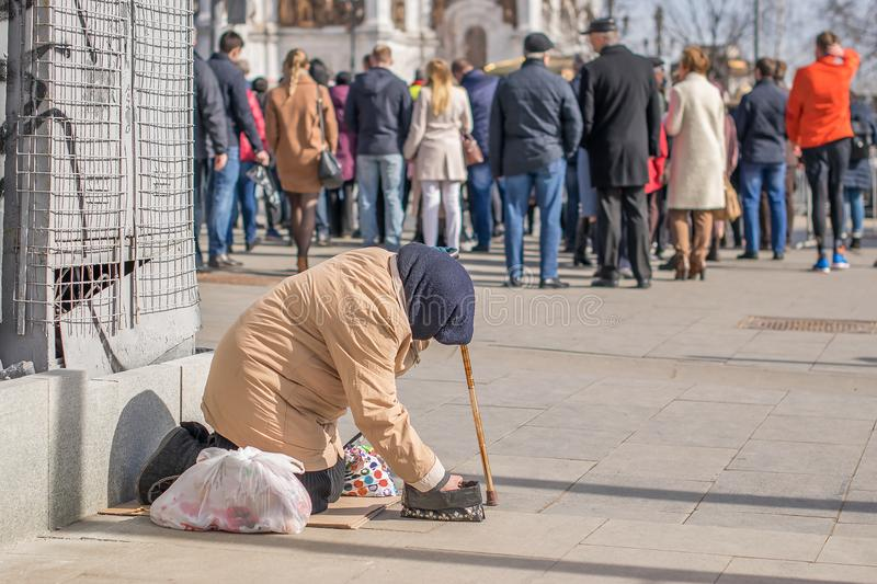 Beggar begging sitting on the ground near the Church and a crowd of people. Poor homeless old woman ragged dirty clothes asks for alms on the street near a crowd royalty free stock photo