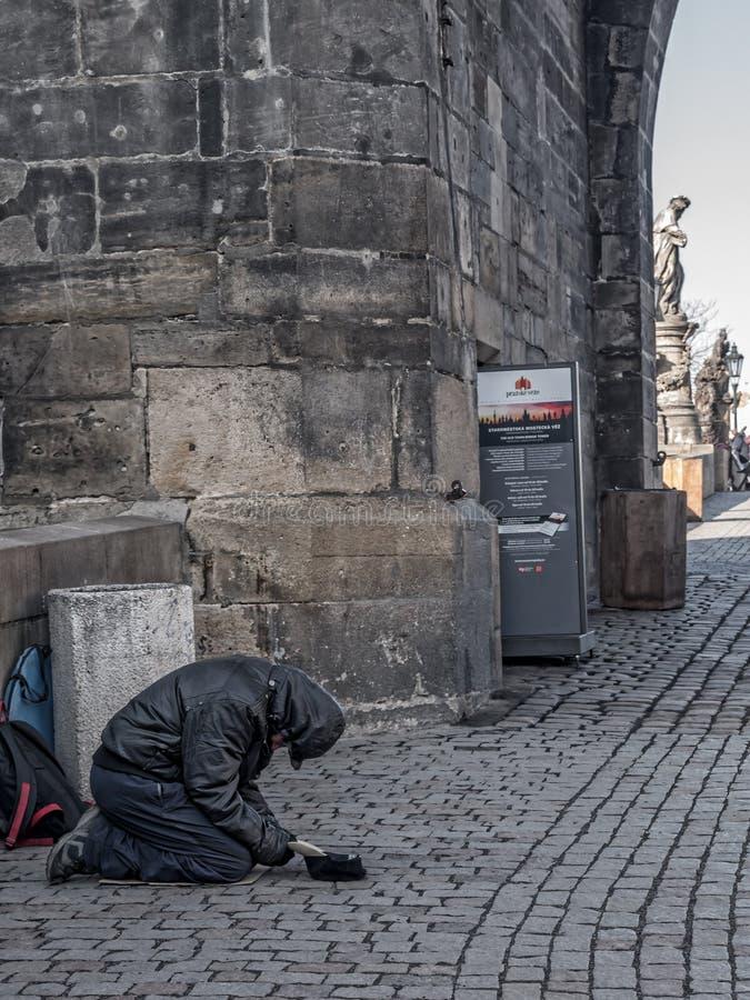 Beggar at the Charles Bridge in Prague. PRAGUE, CZECH REPUBLIC - MARCH 8 2017: Clochard begging for money at the Charles Bridge, Prague, Czech Republic royalty free stock images